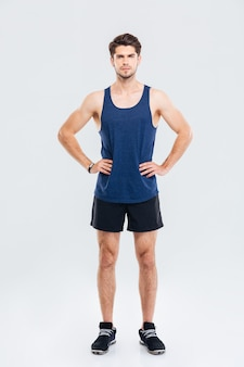 Полный портрет серьезного спортсмена, стоящего с руками на бедрах, изолированного на сером фоне
