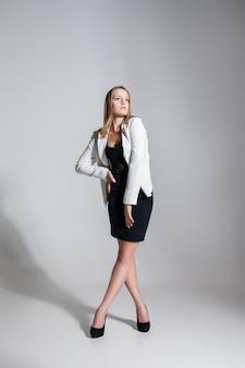 リトルブラックファッションドレスと白いジャケットのセクシーなブロンドの女性の完全な長さの肖像画