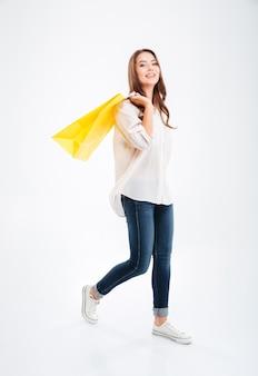 Портрет улыбающейся привлекательной женщины в полный рост, держащей хозяйственные сумки, изолированные на белой стене