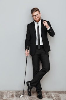 Полная длина портрет улыбающегося бородатого бизнесмена в костюме
