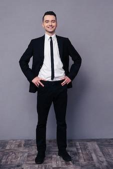 Портрет улыбающегося бизнесмена в полный рост, стоящего на серой стене