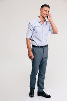 Полный портрет улыбающегося бизнесмена, говорящего по телефону, изолированного на белом
