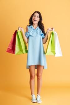 Портрет улыбающейся случайной девушки в полный рост, держащей изолированные хозяйственные сумки