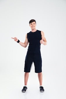 Полнометражный портрет улыбающегося фитнес-человека, показывающего большой палец вверх и указывающего пальцем вдали, изолированы