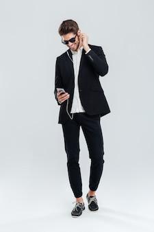 Портрет улыбающегося счастливого молодого бизнесмена в полный рост, слушающего музыку в наушниках и смартфоне над серой стеной