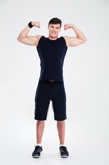 Портрет улыбающегося человека в полный рост, показывающий его изолированные бицепсы