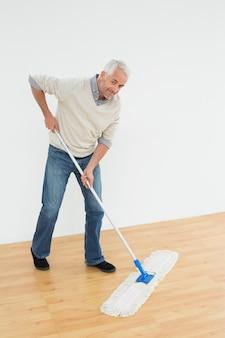 床をモップしている笑顔の成熟した男の全身の肖像画