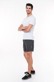 白い背景で隔離の腕を組んで立っている笑顔のスポーツ選手の全身像