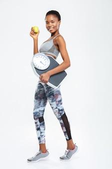 Портрет улыбающейся женщины в полный рост, держащей весы и яблоко, изолированную на белой стене