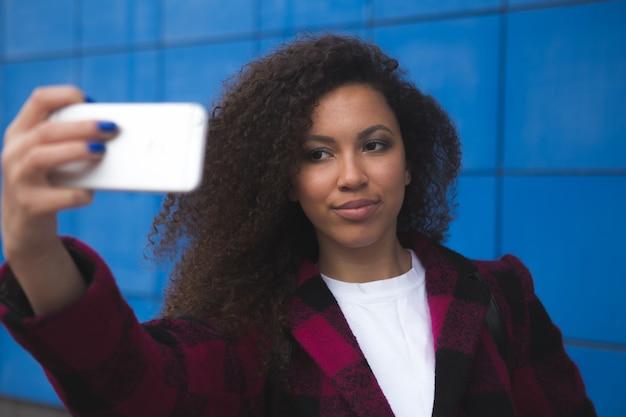 オレンジ色の背景にスマートフォンで自撮り写真を作る笑顔の女性の全身像
