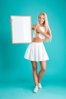 Полный портрет улыбающейся молодой блондинки, стоящей и указывающей пальцем на пустую доску, изолированную на синей стене