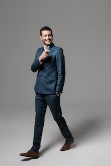 Портрет улыбающегося молодого бизнесмена в полный рост, одетого в костюм, идущего изолированно по серой стене, указывая в сторону