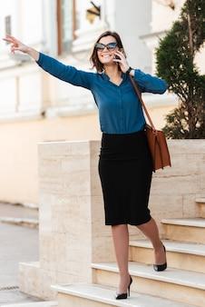 Полная длина портрет улыбающейся молодой женщины в солнцезащитных очках