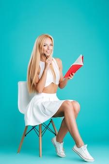 Портрет улыбающейся молодой женщины в полный рост, делая заметки, сидя на стуле, изолированном на синем фоне