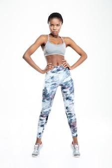 Полный портрет спортивной афро-американской женщины, стоящей изолированной на белом фоне