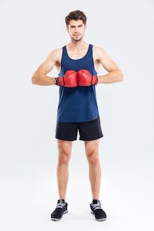회색 배경에 고립 된 빨간 권투 글러브와 스포츠 남자의 전체 길이 초상화