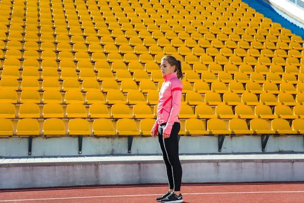 Портрет в полный рост спортивной женщины, стоящей на стадионе
