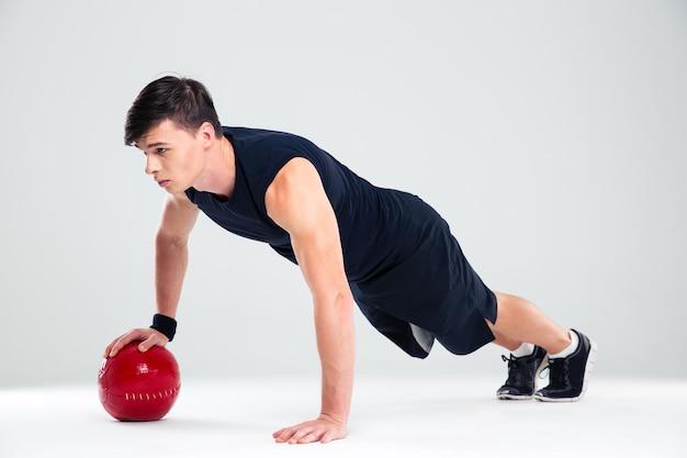 分離されたフィットネス ボールでトレーニング スポーツマン男の完全な長さの肖像画