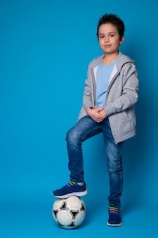 サッカーをするためにボールの上に立っている10代の少年の全身像。コンセプト、サッカー選手