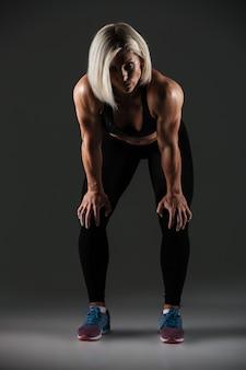 疲れている女性のスポーツウーマンの完全な長さの肖像画