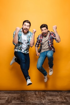 Полная длина портрет двух возбужденных молодых людей, празднующих