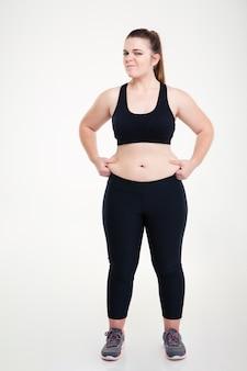 白い壁に隔離された彼女の腹に脂肪をつまむ女性の全身像