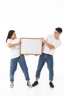 Полный портрет молодой сердитой привлекательной пары, стоящей изолированно над белой стеной, представляя пустую доску
