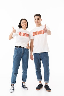 Портрет молодой привлекательной пары в полный рост, стоящей изолированно над белой стеной, одетых в футболки добровольцев, показывает палец вверх