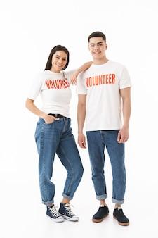 Портрет молодой привлекательной пары в полный рост, стоящей изолированно над белой стеной в футболках добровольцев
