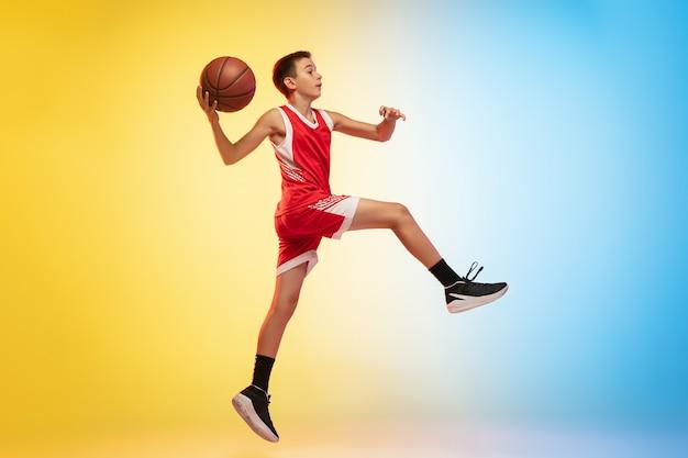 グラデーションの背景にボールを持つ若いバスケットボール選手の全身像