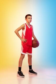Портрет молодого баскетболиста в полный рост с мячом на стене градиента