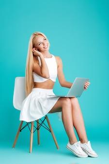 青い背景で隔離のラップトップと椅子に座っている若い陽気な女の子の完全な長さの肖像画