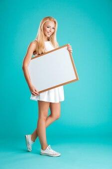 Портрет молодой веселой женщины в полный рост, идущей и держащей пустую доску, изолированную на синей стене