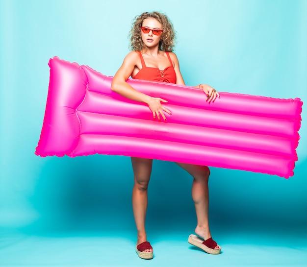 Портрет в полный рост молодой женщины curlu в красном бикини, держащей плавательный розовый матрас у зеленой стены