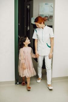 手をつないで、彼女の小さな患者を歯の検査に導く若いかわいい小児歯科医の全身像。