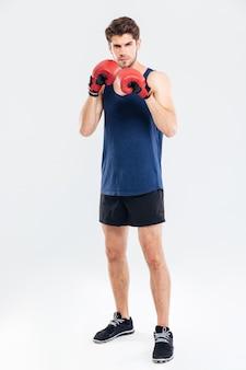 빨간 장갑에 권투와 회색 배경에 고립 된 카메라를보고 젊은 잘 생긴 스포츠 남자의 전체 길이 초상화