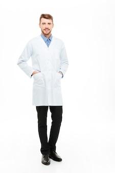 立って、白い背景で隔離のカメラを見ている若い男性医師の完全な長さの肖像画