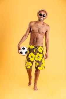 Портрет молодого человека в полный рост, держащего пляжный мяч на оранжевой стене
