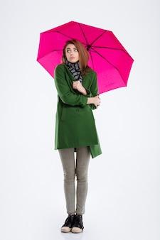 Полный портрет молодой женщины, стоящей под зонтиком, изолированной на белом фоне