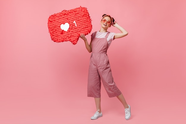 ピンクの衣装とサングラスのアクティブな女性の全身像は、サインのように保持し、孤立した背景にジャンプします。