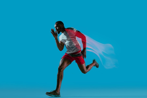 파란색 스튜디오에서 격리된 활동적인 젊은 아프리카 근육질의 달리기 남자의 전체 길이 초상화
