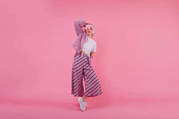 사랑스러운 유럽 여성의 전신 초상화는 사진 촬영 중에 분홍색 줄무늬 바지와 모피 재킷을 입고 있습니다. 트렌디 한 옷을 입고 포즈를 취하는 짧은 화려한 머리를 가진 세련된 소녀