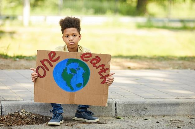 아프리카 계 미국인 소년의 전체 길이 초상화는 하나의 지구 기호를 들고 야외에서 자연을 위해 항의하는 동안 카메라를보고 공간을 복사