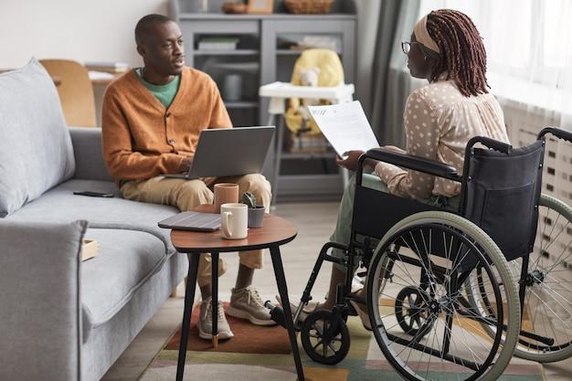 집에서 함께 일하는 장애인 여성과 함께 하는 아프리카계 미국인 부부의 전체 길이 초상화