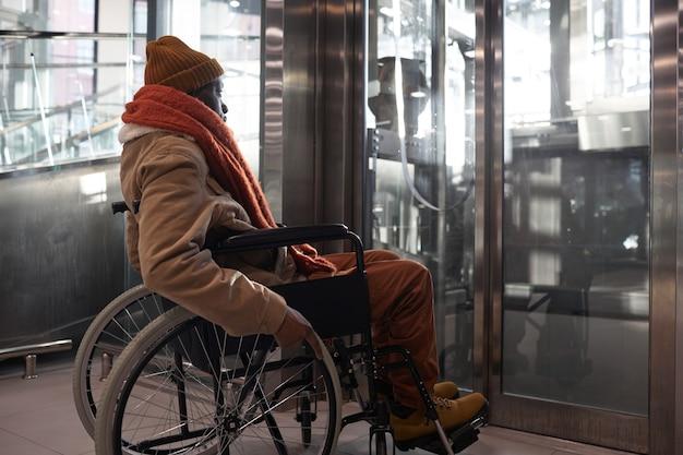 Портрет афроамериканца в инвалидной коляске в полный рост, использующего доступный лифт в городских условиях города, копия пространства