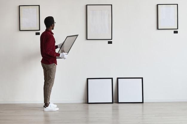 Портрет афроамериканца в полный рост, планирующий художественную галерею или выставку, устанавливая рамки на белой стене,