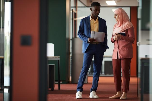 若いイスラム教徒の実業家と話し、現代のオフィスのインテリア、コピースペースに立っている間文書を保持しているアフリカ系アメリカ人の男性の全身像
