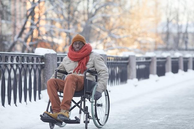 Портрет афроамериканца в полный рост, использующего инвалидную коляску на открытом воздухе зимой и смотрящего в камеру, копией пространства