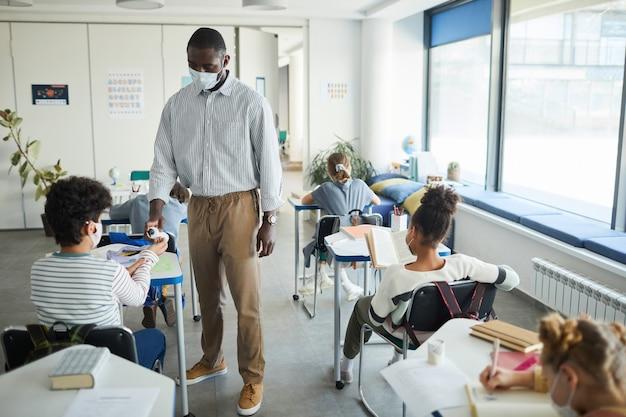 학교 교실에서 아이들의 손을 소독하는 아프리카계 미국인 교사의 전체 길이 초상화, 복사 공간