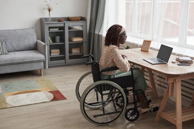 最小限の灰色のインテリア、コピースペースでラップトップと机に座っている間ビデオチャットで呼び出す車椅子のアフリカ系アメリカ人の女性の完全な長さの肖像画